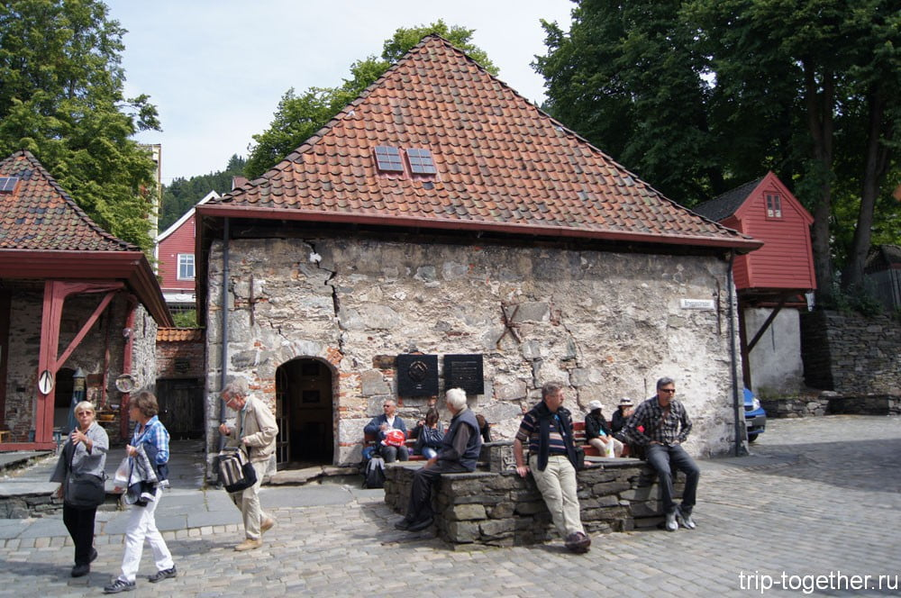 Люди сидят на парапете старинного колодца