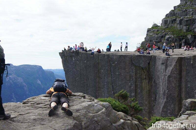 Туристы смотрят в пропасть с утеса Прекистулен