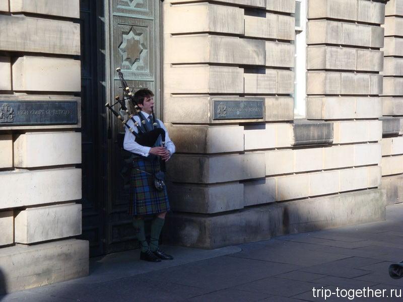 Волынщик в национальной одежде на улице в Эдинбурге