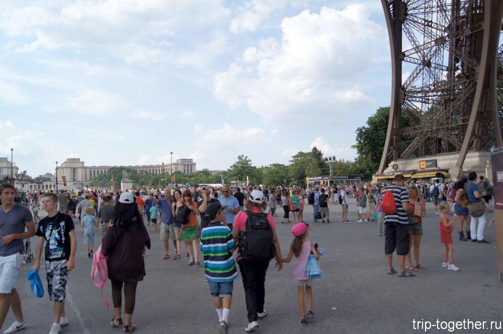 Толпы народа, прогуливающиеся под Эйфелевой башней