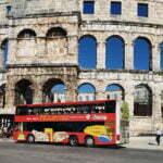 Туристический автобус на фоне Арены Пулы